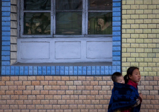 North Korean pioneer girl carrying her brother on her back, Kangwon Province, Wonsan, North Korea