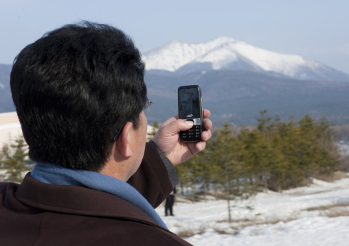 North Korean man taking picture of mount Paektu with his mobile phone, Ryanggang Province, Samjiyon, North Korea