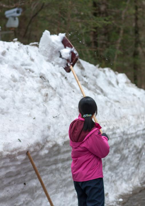 North Korean woman removing snow in the former secret camp of the Korean resistance against japanese, Ryanggang Province, Samjiyon, North Korea