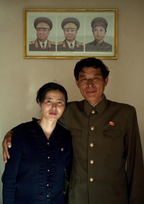 North Korean couple posing in front of the official portraits of the Dear Leaders, North Hamgyong Province, Jung Pyong Ri, North Korea