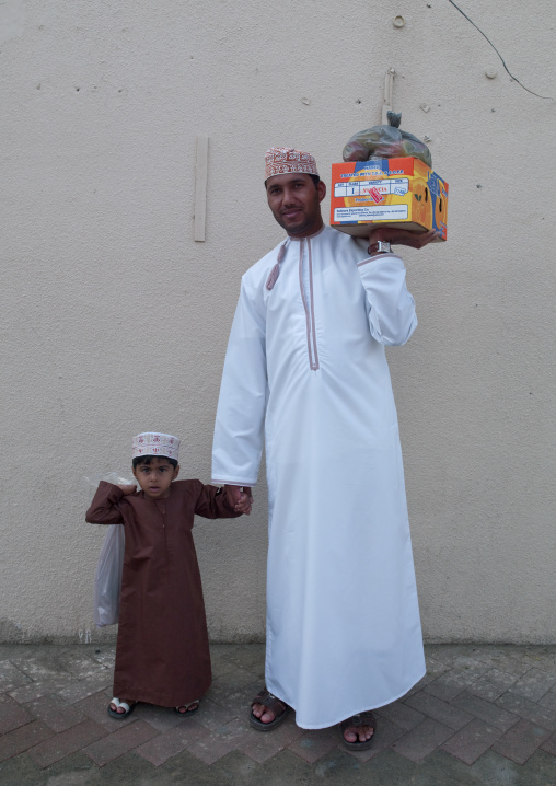 Father And Son Both Wearing Traditional Dishdasha And Carring Goods, Ibra, Oman