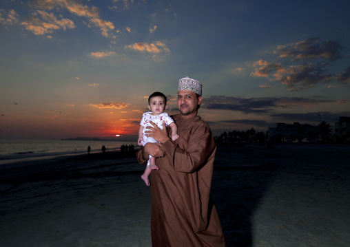 Man Holding His Baby Standing On The Beach At Dusk, Salalah, Oman