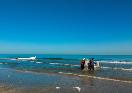 Omani fishermen pushing a boat in the sea, Al Batinah, Barka, Oman
