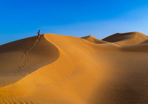 Tourist woman climbing a dune in the rub al khali desert, Dhofar Governorate, Rub al Khali, Oman