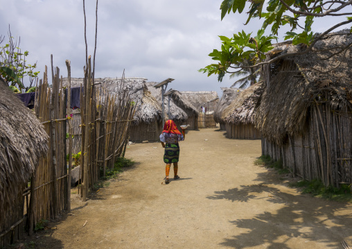 Panama, San Blas Islands, Mamitupu, Kuna Woman Passing In Front Traditional Houses With A Solar Panel