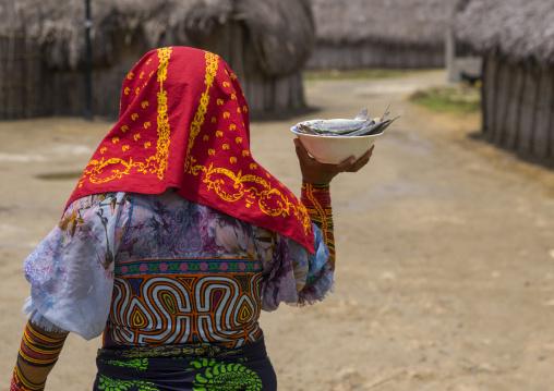 Panama, San Blas Islands, Mamitupu, Kuna Indian Woman Carrying Fish In A Bowl