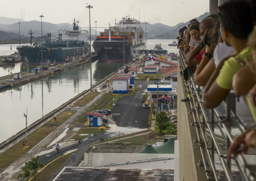 Panama, Province Of Panama, Panama City, Tourists Watching Container Ship Passing Through The Miraflores Locks In The Panama Canal