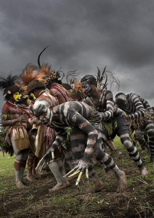 Snake men with hulis warriors during a sing-sing under a storm, Western Highlands Province, Mount Hagen, Papua New Guinea