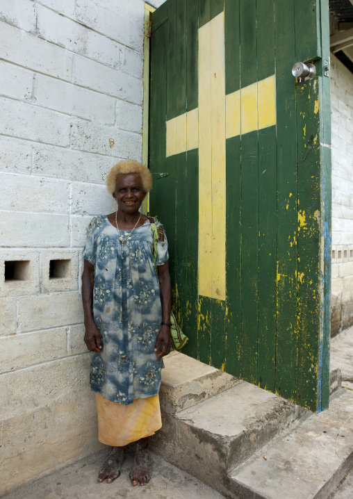 Old woman in front of a church entrance, New Ireland Province, Langania, Papua New Guinea