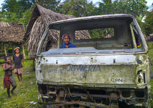 Children playing in a car wreck, Milne Bay Province, Trobriand Island, Papua New Guinea