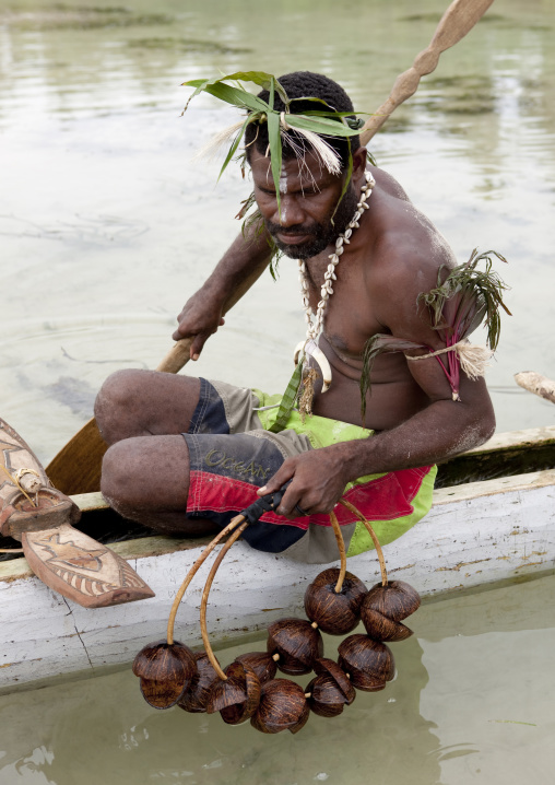 Man on a pirogue making a shark calling with coconut rattle, New Ireland Province, Kavieng, Papua New Guinea