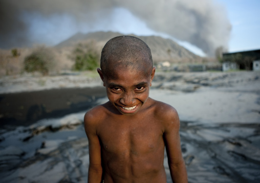 Boy under a volcanic eruption in tavurvur volcano, East New Britain Province, Rabaul, Papua New Guinea
