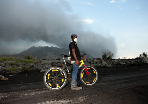 Boy with his bike in tavurvur volcano, East New Britain Province, Rabaul, Papua New Guinea