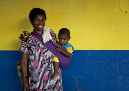 Mother and child in front of a colorful wall, East New Britain Province, Rabaul, Papua New Guinea