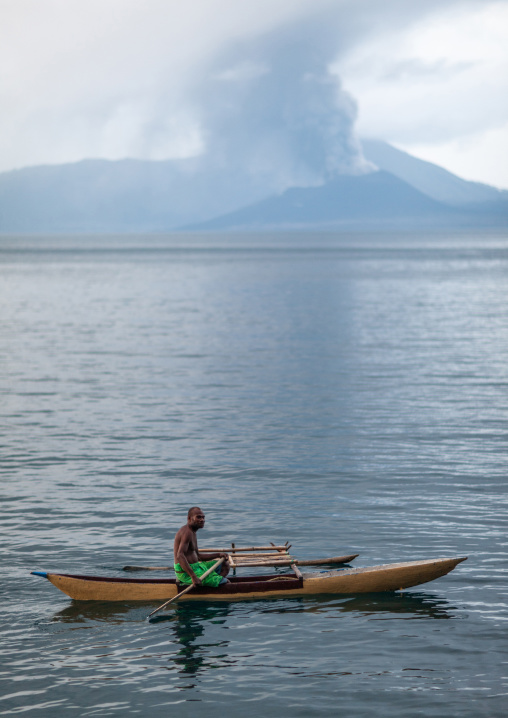 Man on a canoe in front of a volcanic eruption in Tavurvur volcano, East New Britain Province, Rabaul, Papua New Guinea