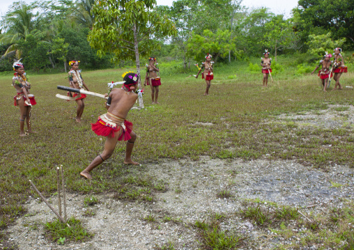 Girls in traditional clothing playing cricket, Milne Bay Province, Trobriand Island, Papua New Guinea