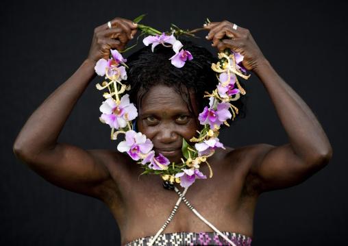 Woman putting a floral necklace around her neck, Autonomous Region of Bougainville, Bougainville, Papua New Guinea