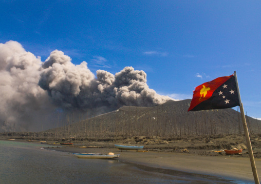 Papuan flag in front of Tavurvur volcano in eruption, East New Britain Province, Rabaul, Papua New Guinea