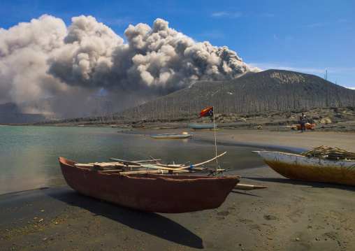 Boats in front of a volcanic eruption in Tavurvur volcano, East New Britain Province, Rabaul, Papua New Guinea