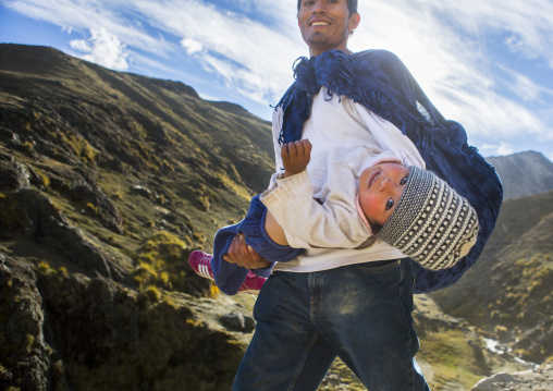Peruvian Father Carrying His Baby On The The Way To Qoyllur Riti Festival, Ocongate Cuzco, Peru