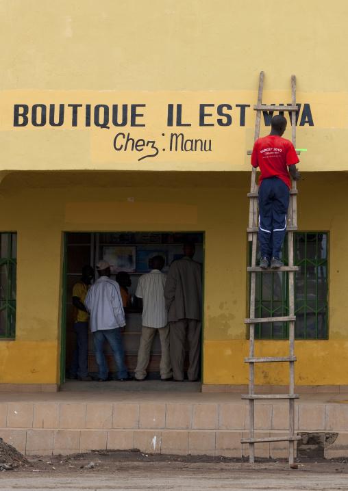 Rwandan man painting his shop wall on a ladder, Lake Kivu, Gisenye, Rwanda