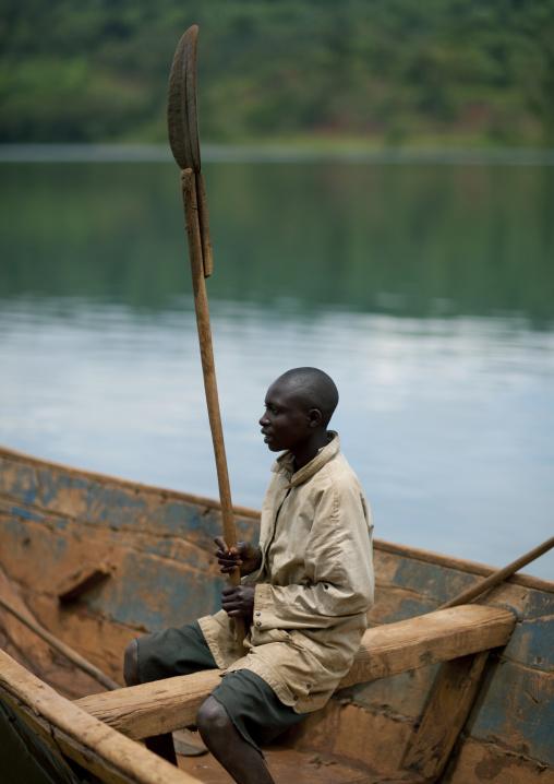 Rwandan man inside a boat holding a row, Lake Kivu, Nkombo, Rwanda