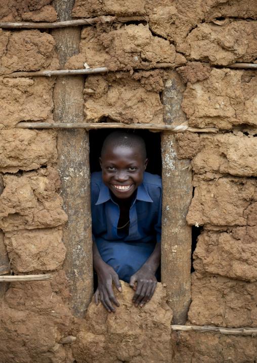 Batwa tribe boy looking though a window, Western Province, Cyamudongo, Rwanda