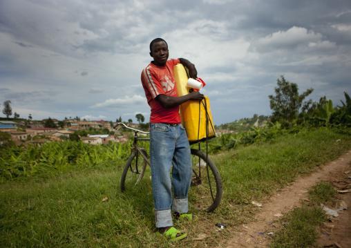 Rwandan man putting a jerrycan on his bicycle, Kigali Province, Kigali, Rwanda