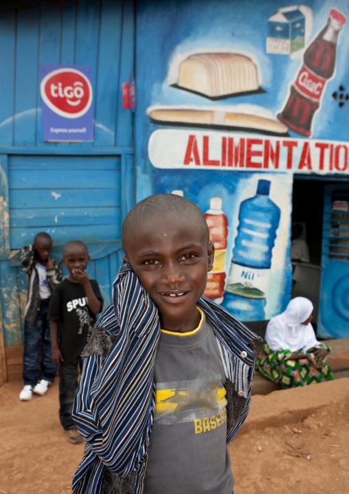 Rwandan boy in front of a shop mural, Kigali Province, Kigali, Rwanda