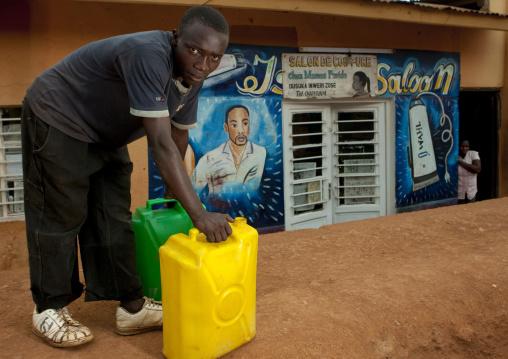Rwandan man with jerrycans in the street, Kigali Province, Kigali, Rwanda