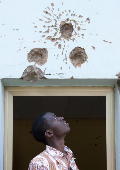 Rwandan man looking at bullets holes in camp kigali memorial site, Kigali Province, Kigali, Rwanda