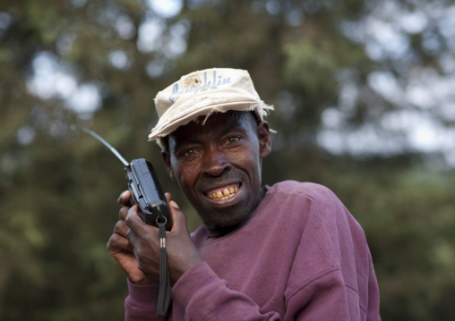 Rwandan man listening tov the radio in the countryside, Northwest Province, Rehengeri, Rwanda