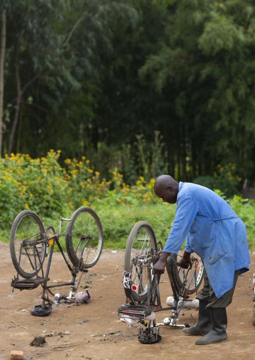 Rwandan man repairing bicycles in the street, Northwest Province, Rehengeri, Rwanda