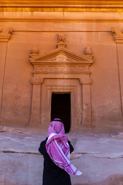 Saudi tourist in front of a tomb in al-Hijr archaeological site in Madain Saleh, Al Madinah Province, Alula, Saudi Arabia
