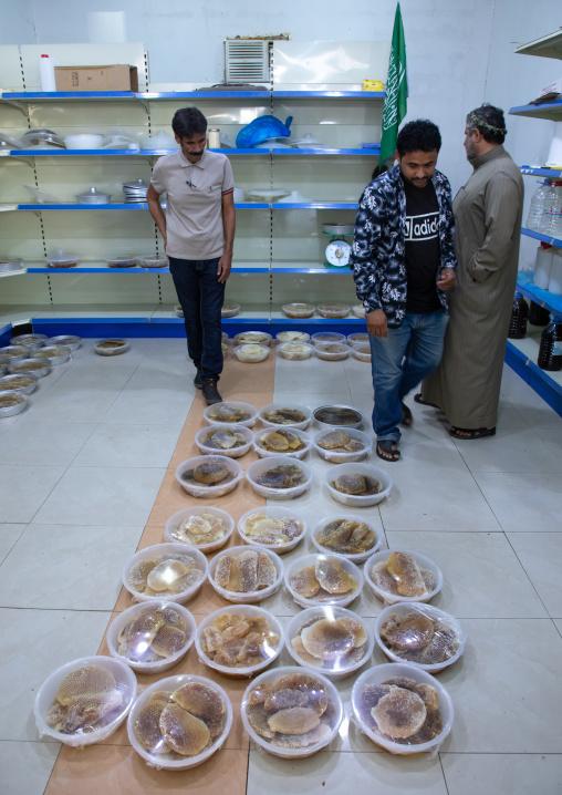Saudi man selling honeycombs and honey in a shop, Asir province, Rijal Alma, Saudi Arabia
