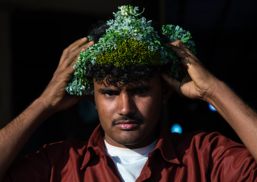 Portrait of a flower man adjusting a floral crown on the head, Jizan province, Sabya, Saudi Arabia