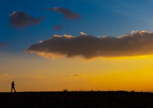Man silhouette in front of a cloudy sunset, Asir province, Dahran Aljanub, Saudi Arabia