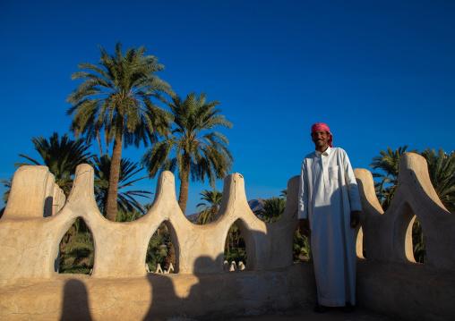 Saudi man standing on the crenelated terrace of his mud house, Najran Province, Najran, Saudi Arabia