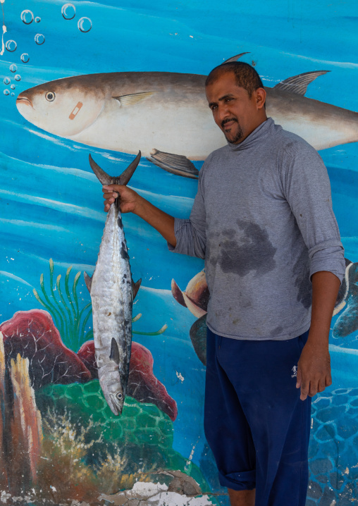 Portrait of faranasi man with a big fish in his hand in front of a mural painting, Red Sea, Farasan, Saudi Arabia