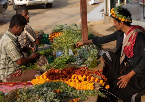A flower vendor preparing and selling floral garlands and crowns on a market, Jizan Province, Mahalah, Saudi Arabia