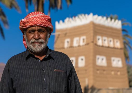 Saudi farmer standing in front of a traditional old mud house, Najran Province, Najran, Saudi Arabia