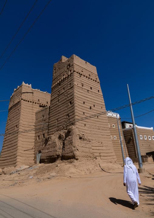 Saudi man passing in front of traditional old mud house, Najran Province, Najran, Saudi Arabia