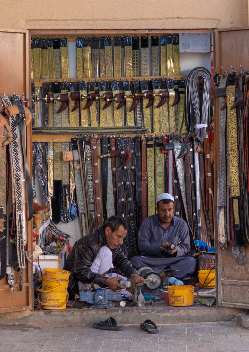 Saudi men prepares a traditional janbiya dagger for sale inside his shop, Najran Province, Najran, Saudi Arabia
