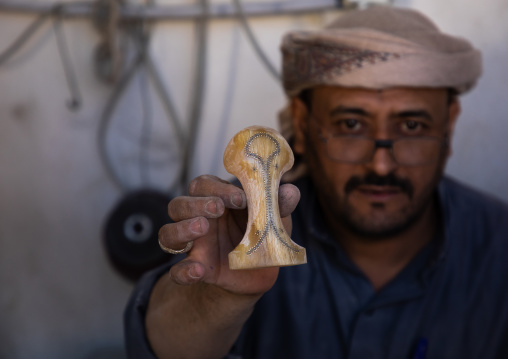 A saudi man prepares a traditional janbiya dagger for sale inside his shop, Najran Province, Najran, Saudi Arabia