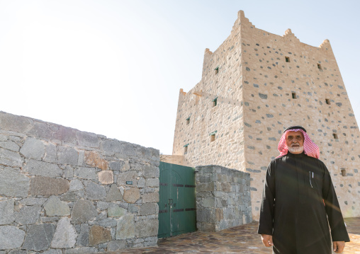 Saudi man standing in front of an old traditional stone house, Asir province, Al-Namas, Saudi Arabia
