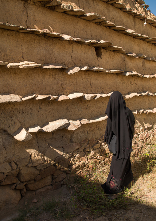 Saudi woman in front of traditional clay and silt homes in a village, Asir Province, Ahad Rafidah, Saudi Arabia