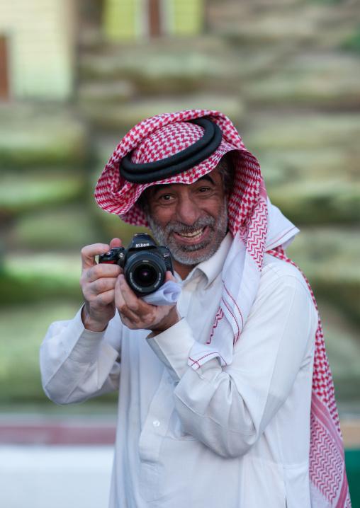 Portrait of a saudi man wearing a kaffiyeh taking pictures, Al-Jawf Province, Sakaka, Saudi Arabia