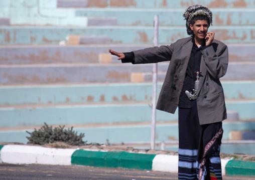 Saudi flower man hitchhiking at roadside, Asir province, Sarat Abidah, Saudi Arabia