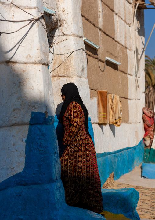 Saudi woman entering a traditional mud-bricks house, Najran Province, Najran, Saudi Arabia