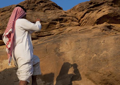Saudi tourist taking pictures of petroglyphs on a rock, Najran Province, Abar Himma, Saudi Arabia